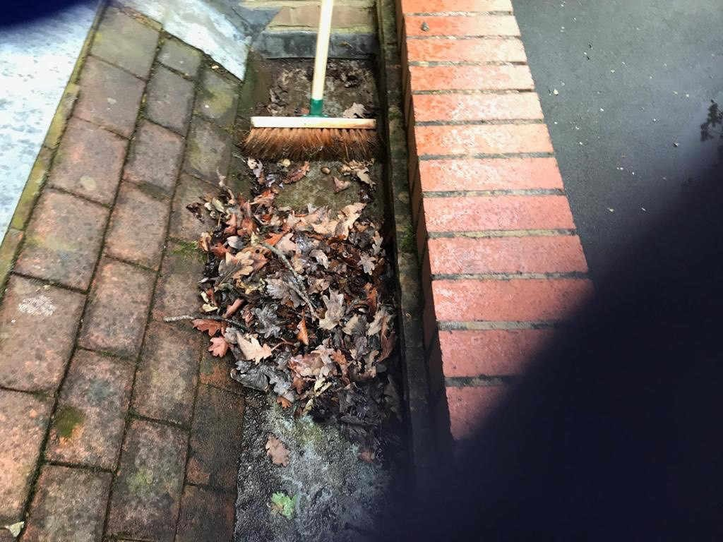 Sweeping up the leaves in the gutter
