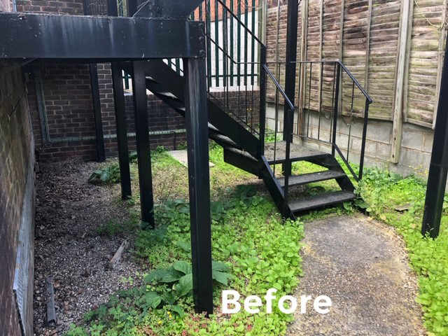 Fire escape staircase, fence and grassed surface before cleaning & repair