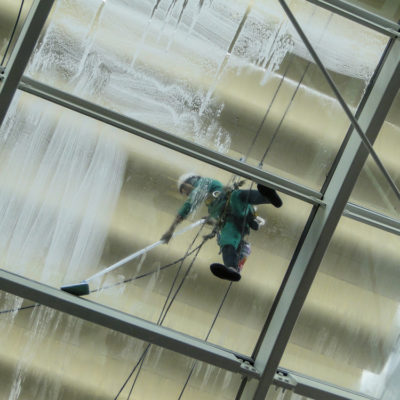 man is cleaning the glass roof of a building with a pressure washer. face is hidden by a scarf.