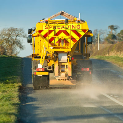winter service vehicle or gritter spreading rock salt on the road surface to prevent icing in winter which causes accidents when vhicles slip on the highway.