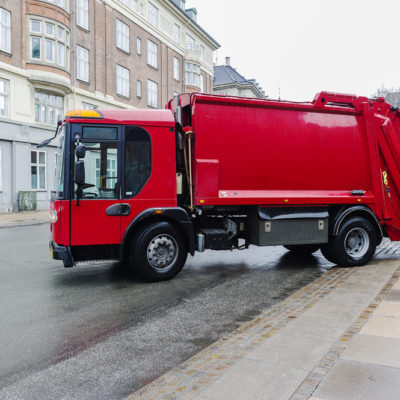 Red garbage disposal truck parked at the side of a street collecting household rubbish and waste for crushing, recycling and treatment or disposal on municipal dumps